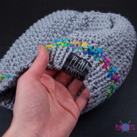 Серая вязаная шапка ручной работы с цветнушкой